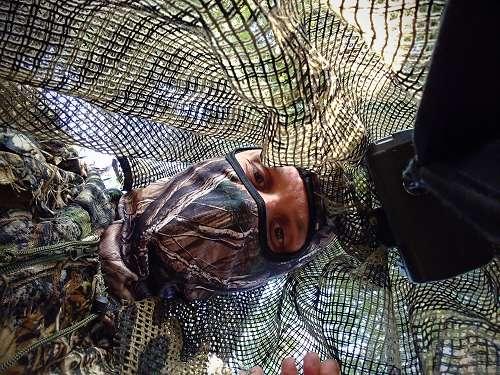 Ansitz mit Tarnanzug und Tarnnetz über Kopf und Kamera geworfen